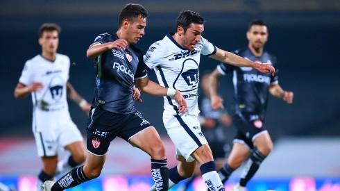 Raul Sandoval (left) of Necaxa struggles for the ball against Juan Vigon (right) of Pumas UNAM.