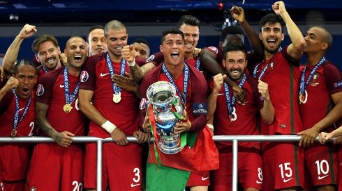 Cristiano Ronaldo of Portugal (center) lifts the 2016 European Championship Trophy. (Getty)