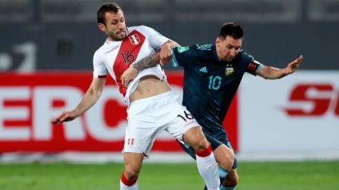 Horacio Calcaterra of Peru (left) tries to hold Lionel Messi of Argentina
