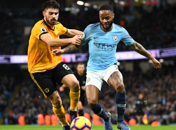 Raheem Sterling of Manchester City (right) is tackled by Ruben Neves of Wolverhampton Wanderers (left). (Getty)