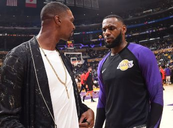 Chris Bosh (left) talks with LeBron James (right) during a Lakers-Raptors game. (Getty)